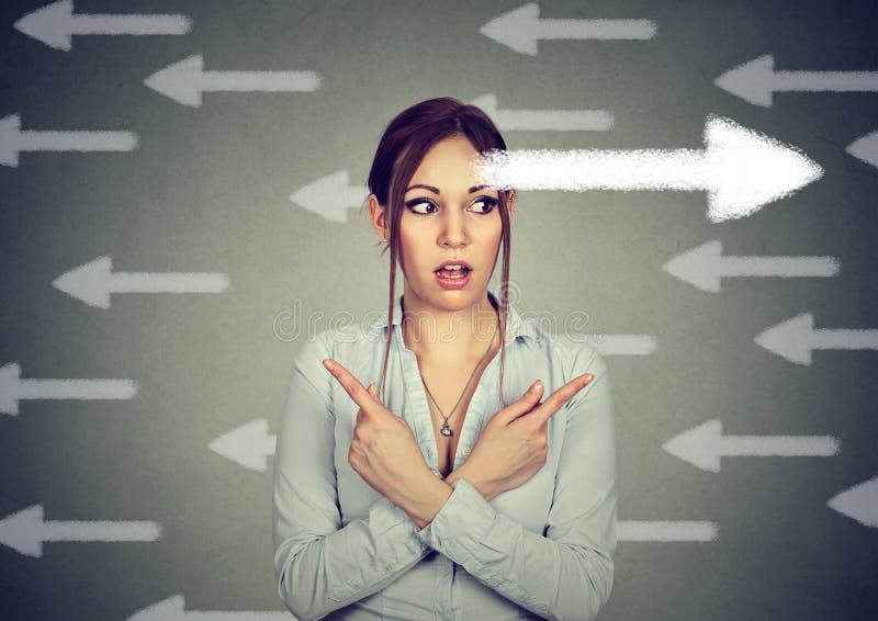 妇女有重新考虑使为难指向手指在另外方向 库存照片
