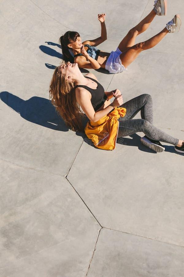 妇女朋友获得乐趣在冰鞋公园 免版税库存图片