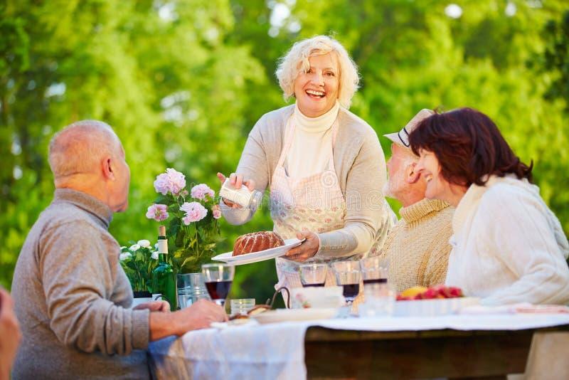 妇女服务在生日聚会的圆环蛋糕 免版税库存图片