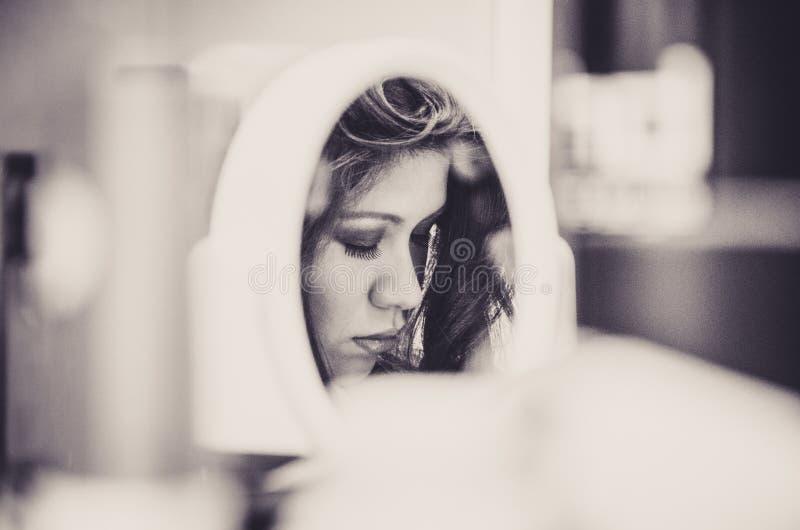 妇女构成通过镜子 库存图片