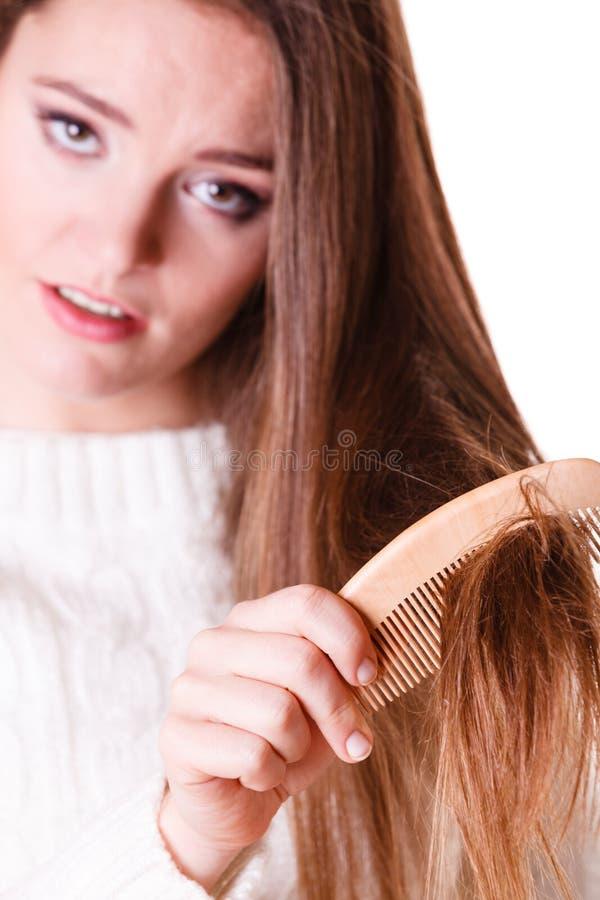 妇女梳和拉扯头发 免版税库存照片