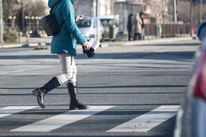 妇女横穿街道和看下来电话 免版税图库摄影