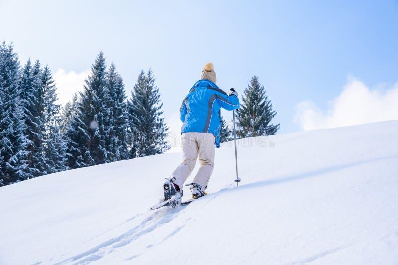 妇女步行与在雪足迹的雪靴在森林冬天风景在奥伯斯特多夫,德国的南部的巴伐利亚阿尔卑斯 库存图片