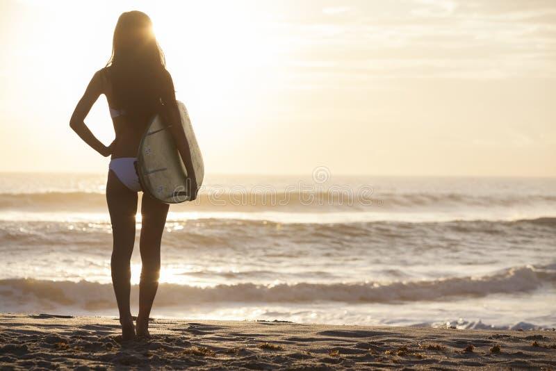 妇女比基尼泳装冲浪者&冲浪板日落海滩 免版税库存图片