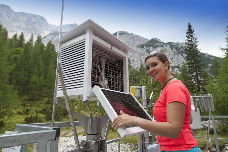 妇女气象学家在山气象台的读书meteodata 库存图片