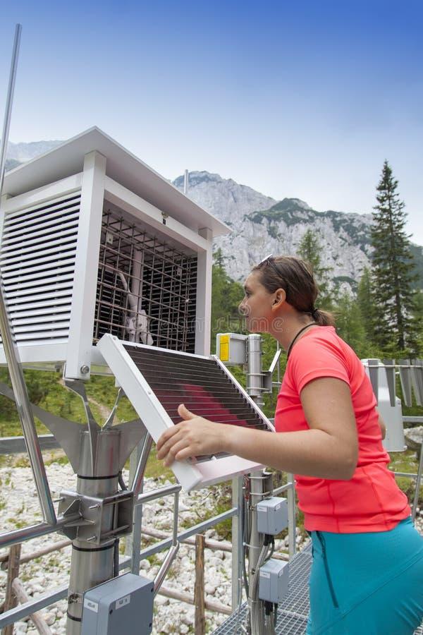 妇女气象学家在山气象台的读书meteodata 免版税库存图片