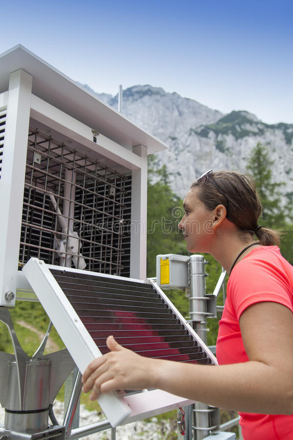 妇女气象学家在山气象台的读书meteodata 免版税库存照片