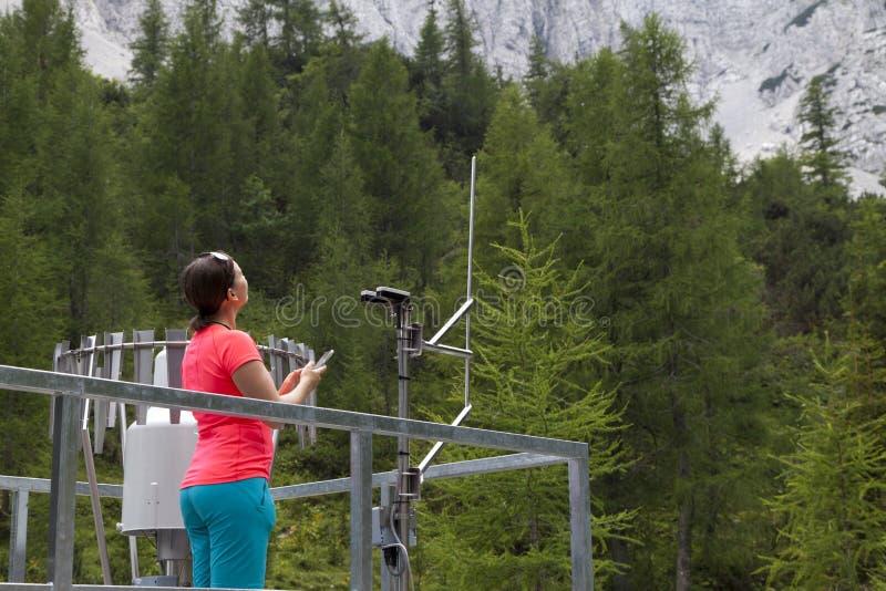 妇女气象学家在山气象台的读书meteodata 图库摄影