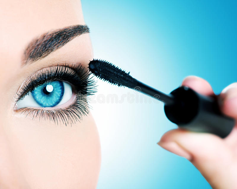 妇女注视与长的黑睫毛和构成刷子 免版税库存照片