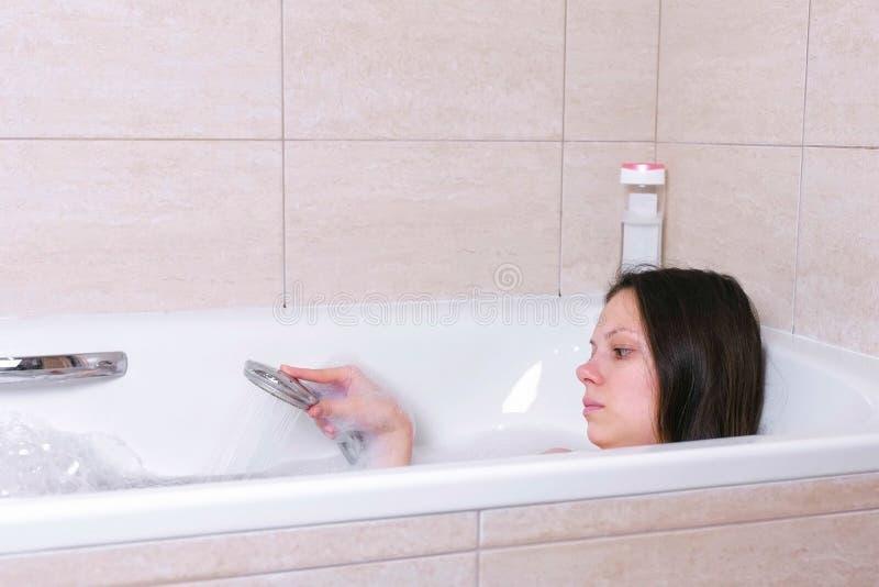 妇女洗与泡沫的浴 她倾吐她的从阵雨的身体水 库存图片