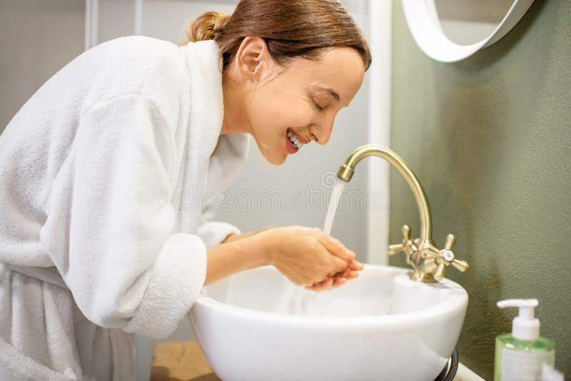 妇女洗涤物面孔在卫生间里 库存照片