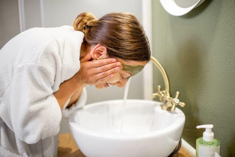 妇女洗涤物面孔在卫生间里 免版税图库摄影