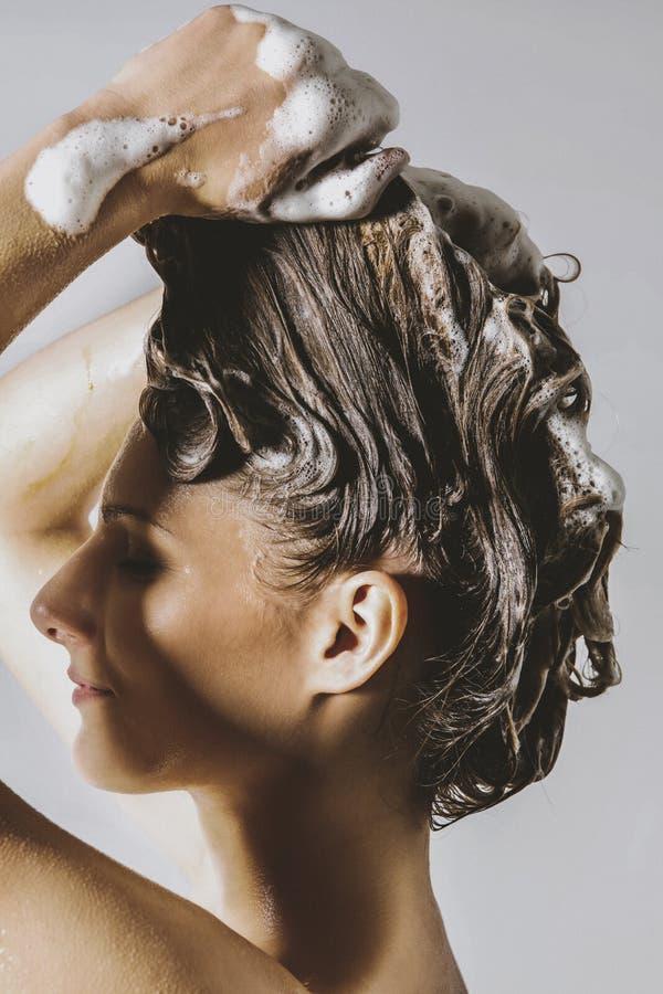 妇女洗涤的头发-护发 免版税图库摄影