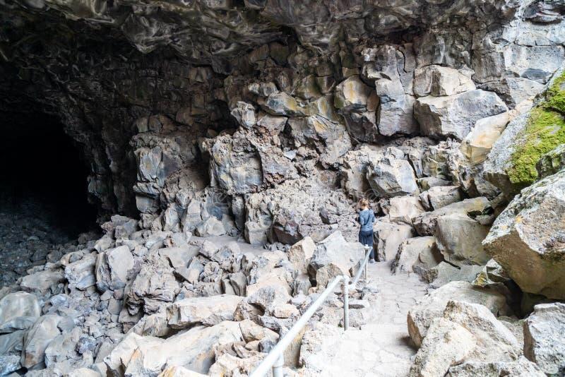 妇女洞探险家步行下来入在火山岩床国家历史文物的头骨洞在加利福尼亚 免版税库存图片