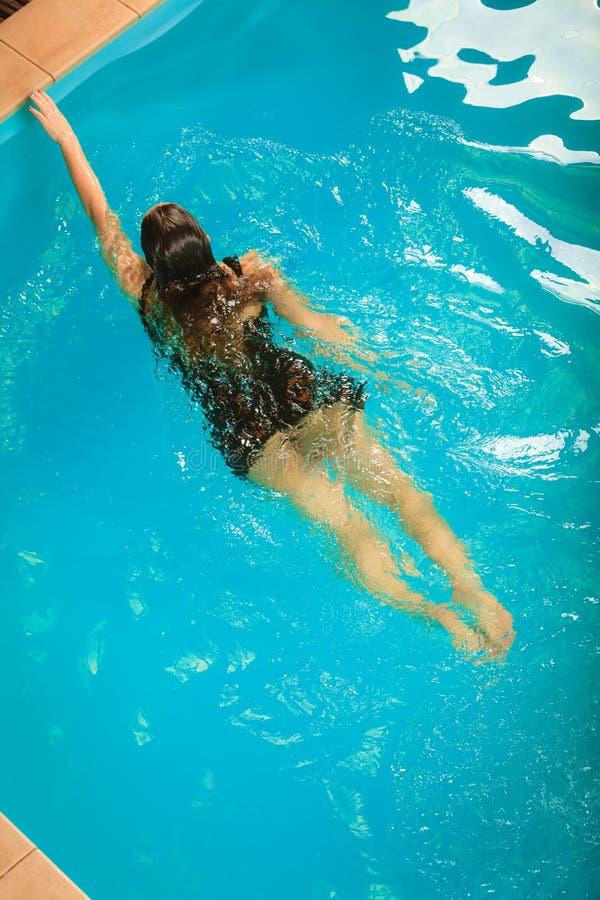 妇女浮动放松在游泳池水中 免版税库存图片