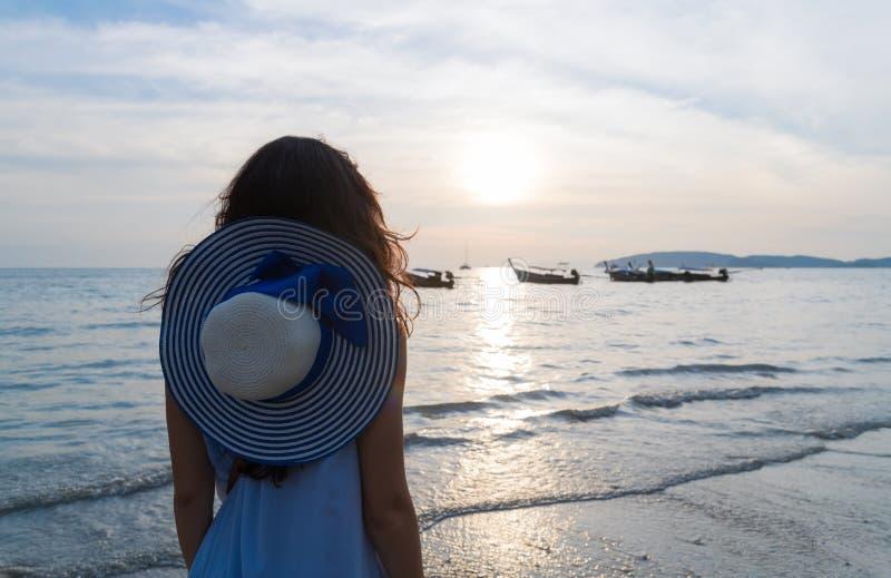 妇女海滩暑假,女孩海日落后面背面图 库存图片