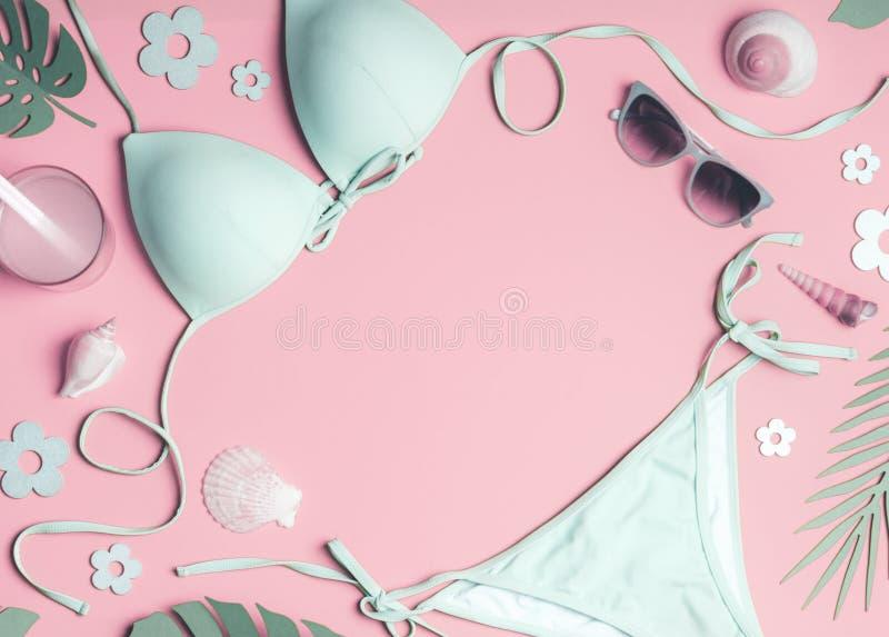 妇女海滩辅助部件框架:比基尼泳装、太阳帽子、凉鞋、太阳镜和袋子、海壳和热带叶子在粉红彩笔 免版税库存照片