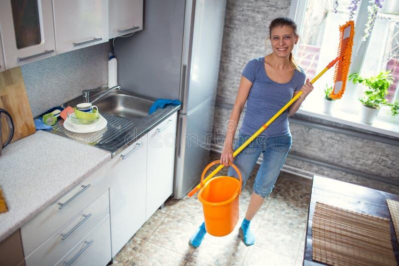 妇女清洁在厨房洗涤地板 库存照片