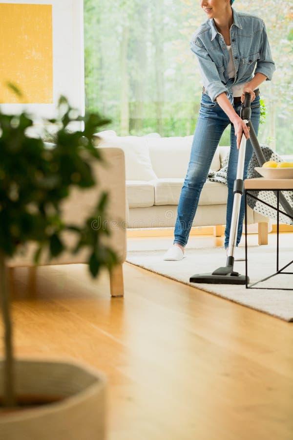 妇女清洁地毯在房子里 免版税库存图片