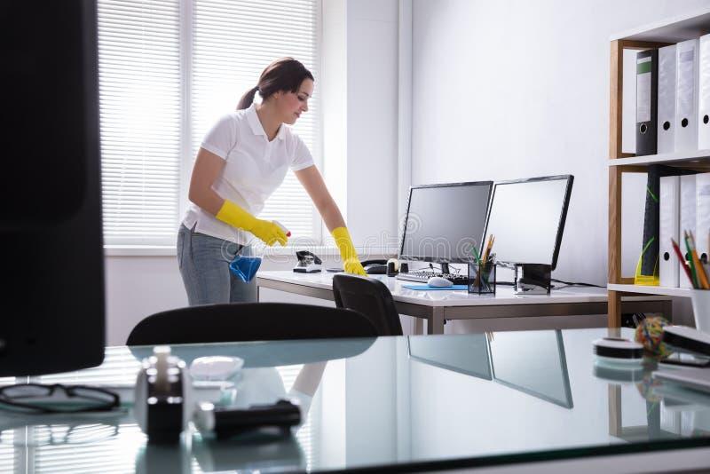 妇女清洁计算机在办公室 免版税库存照片