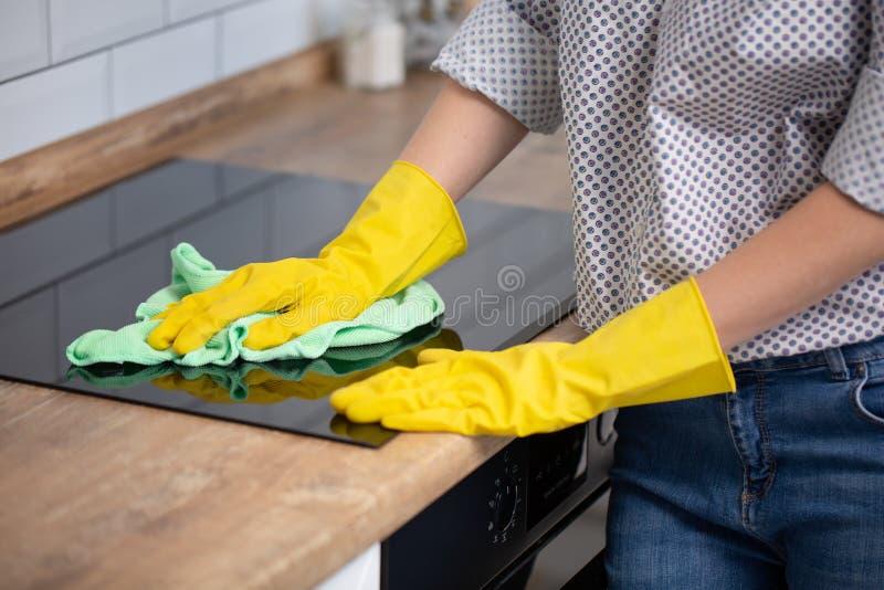 妇女清洗的归纳上面,在黄色橡胶手套擦亮剂火炉cooktop,特写镜头,没有面孔的手 清楚的厨房器具 库存照片