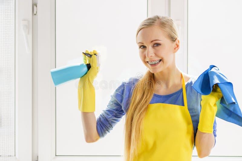 妇女清洗的窗口在家 库存照片
