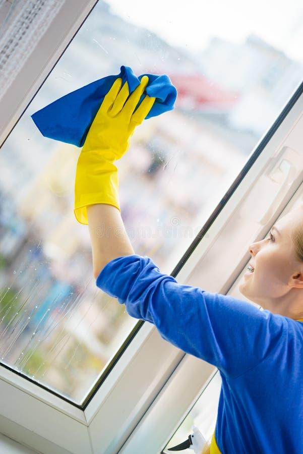 妇女清洗的窗口在家 免版税库存图片