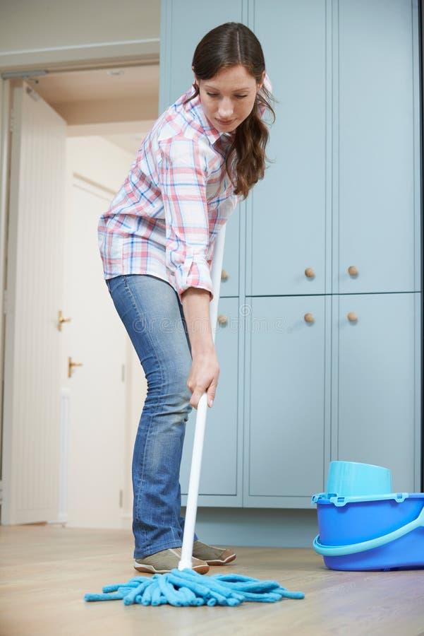 妇女清洁与拖把的厨房地板 库存照片