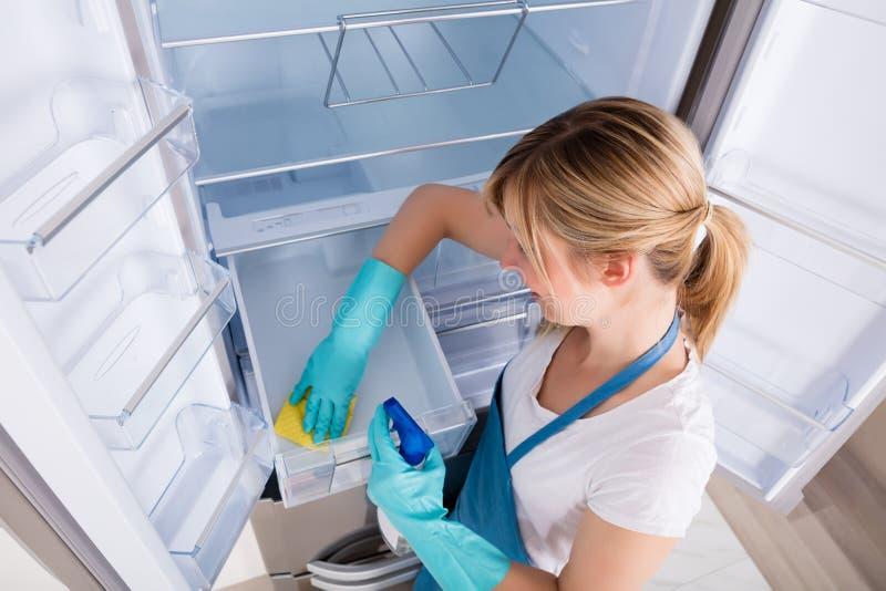 妇女清洁冰箱大角度看法  免版税库存图片
