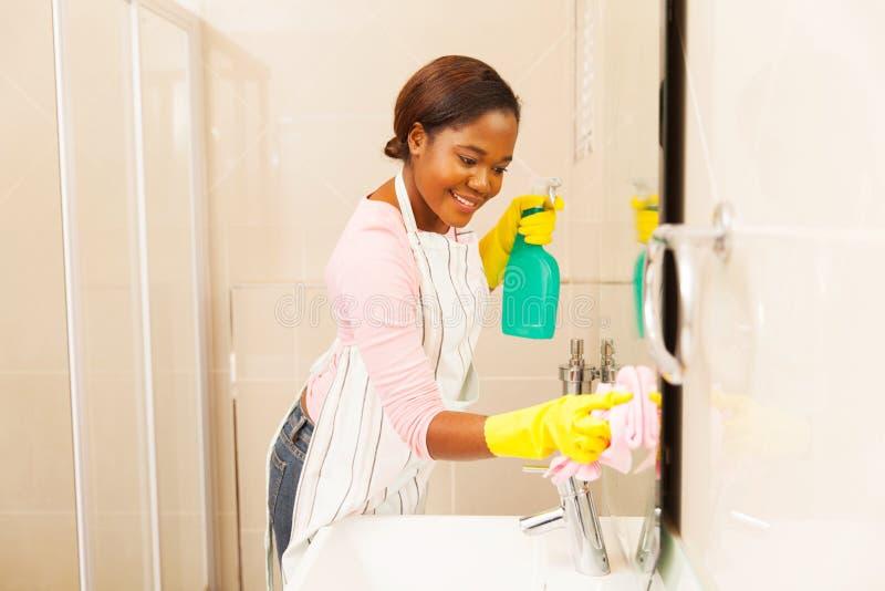 妇女清洁卫生间镜子 免版税库存照片