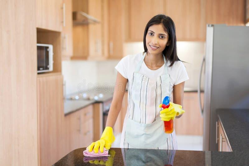 妇女清洁厨台 图库摄影