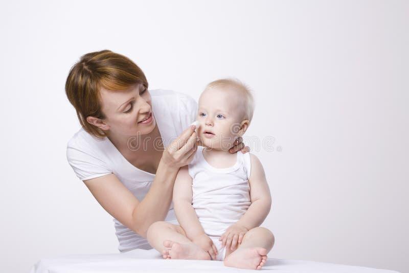 妇女清洁婴孩的面孔 免版税库存照片