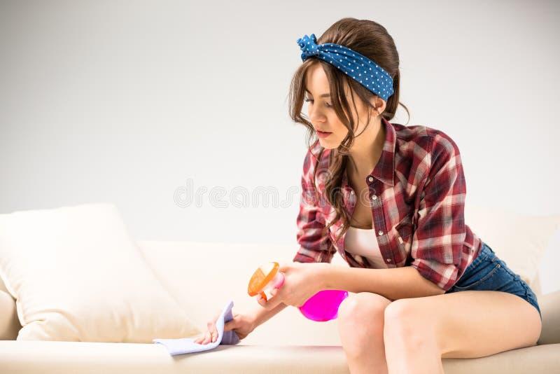 妇女清洁沙发 库存图片