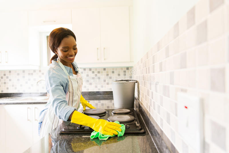 妇女清洁火炉 免版税库存图片