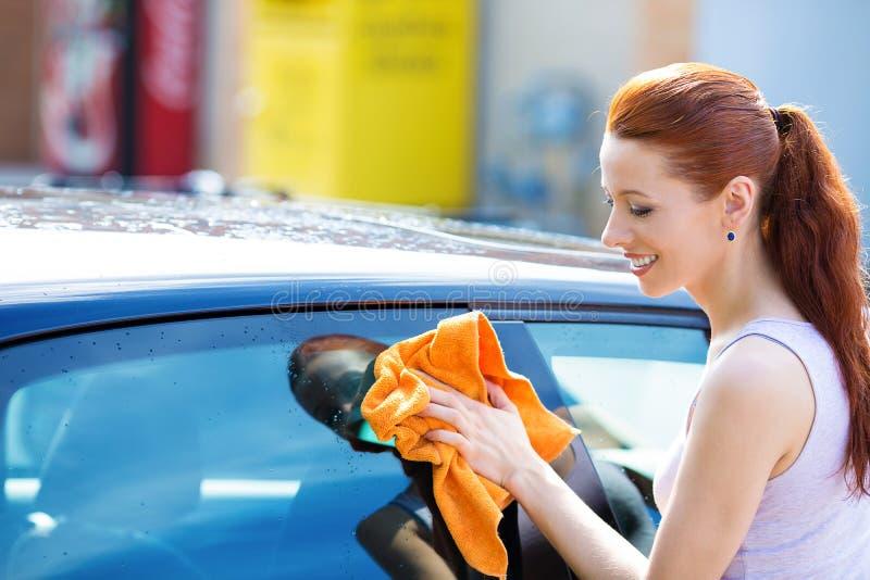 妇女清洁,干燥抹她的黑汽车在夏天晴天 免版税库存照片