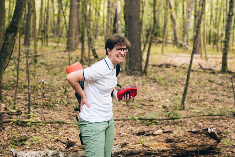 妇女游人在森林里得到了背部受伤并且受到伤害 健康问题在旅途上 题材保险公司 在脊椎的痛苦 免版税库存照片