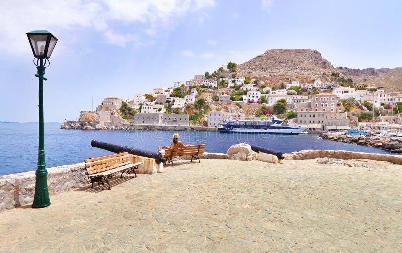 妇女游人看九头蛇海岛希腊风景  免版税图库摄影