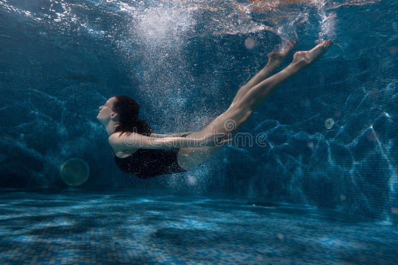 妇女漂浮在水池的水下 免版税图库摄影