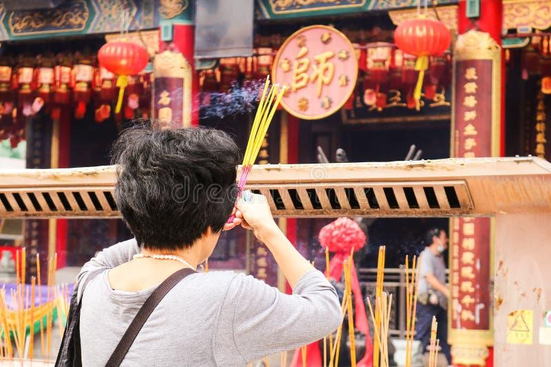 妇女灼烧的香火为在中国寺庙祈祷 免版税库存照片