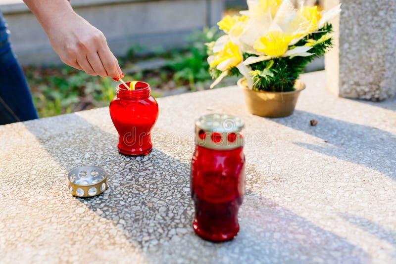 妇女点燃一个蜡烛在坟墓 免版税库存照片