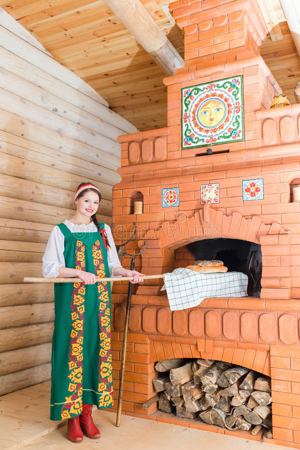 妇女烘烤在俄国火炉的面包 库存图片