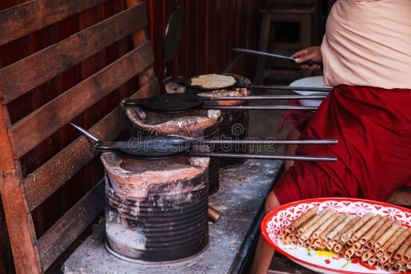 妇女烘烤的皮带Muan泰国酥脆椰子薄酥饼劳斯快餐相似与在热的模子平底锅的pirouline在木炭土制火炉 免版税库存照片