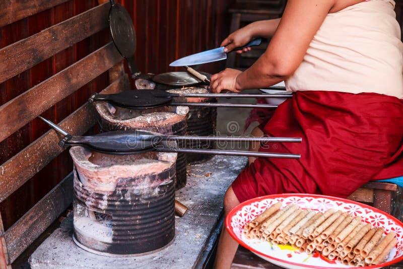 妇女烘烤的皮带Muan泰国酥脆椰子薄酥饼劳斯快餐相似与在热的模子平底锅的pirouline在木炭土制火炉 库存图片