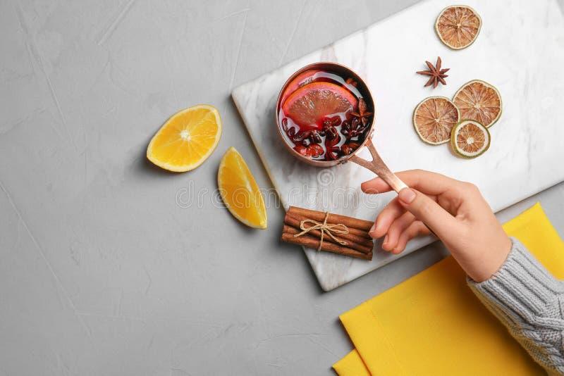 妇女热的加香料的热葡萄酒藏品平底深锅在桌上的 库存照片