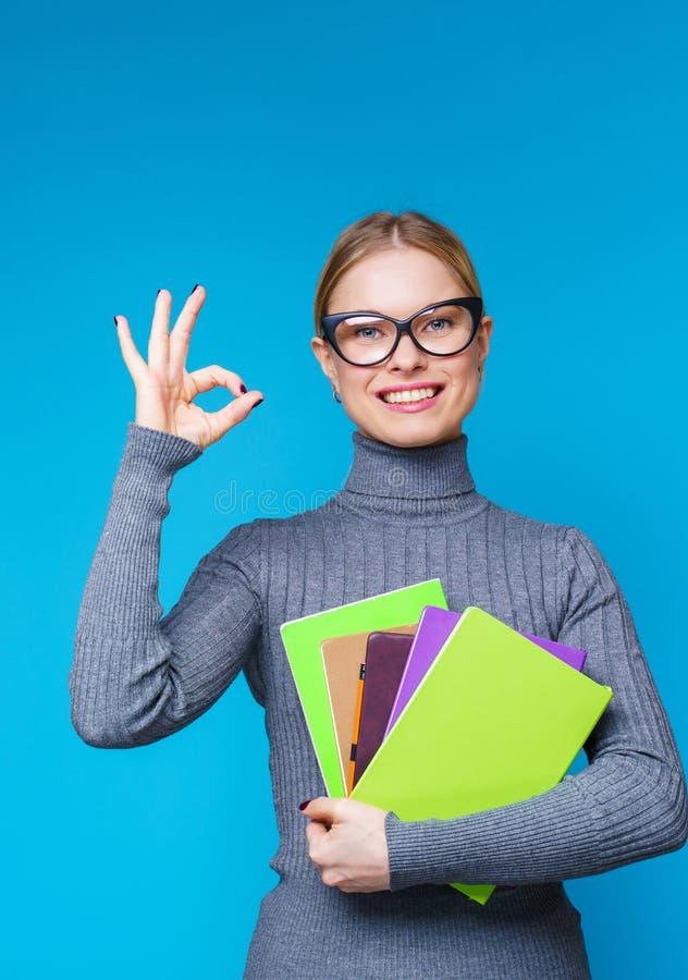 妇女照片玻璃的与书在看照相机的手上 免版税图库摄影