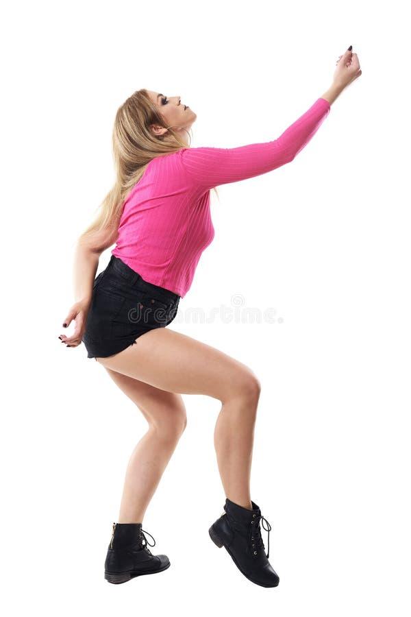 妇女爵士乐跳舞与被举的胳膊和查寻的芭蕾舞蹈艺术姿势侧视图  免版税库存照片
