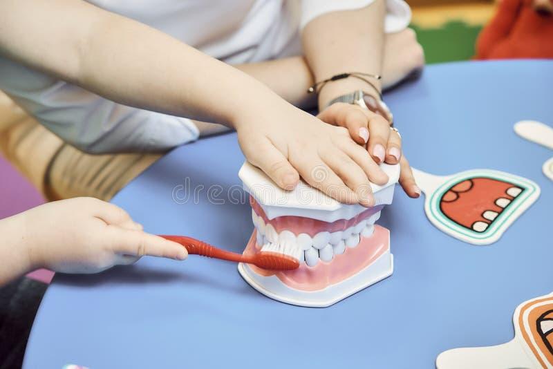 妇女牙医教女孩刷她的牙 免版税图库摄影