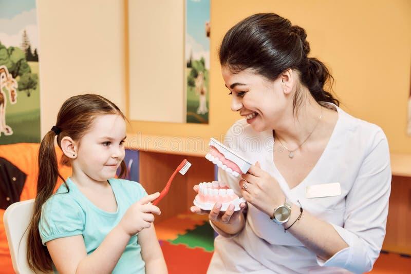 妇女牙医教女孩刷她的牙 免版税库存图片