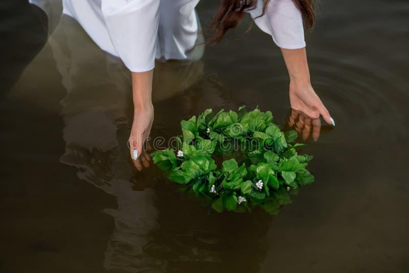 妇女特写镜头白色礼服的在水中 有花圈的艺术妇女在河 湿巫婆女孩在湖 免版税库存图片
