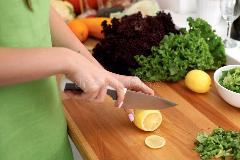 妇女特写镜头在厨房里递烹调菜沙拉 主妇切柠檬 健康膳食和素食主义者概念 免版税库存照片